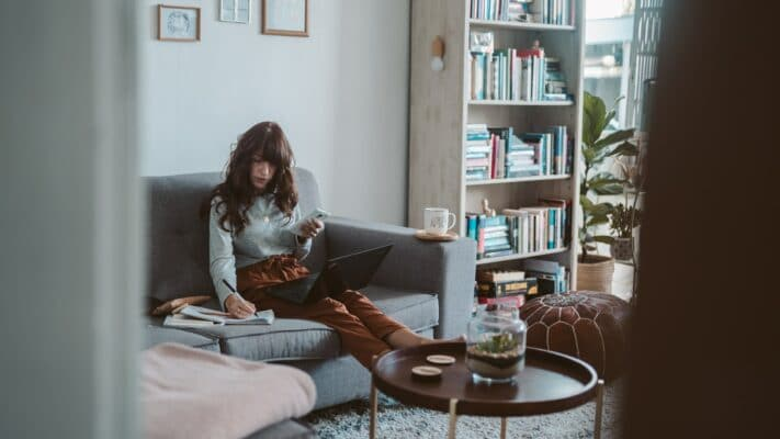 Dame arbeitet im Wohnzimmer neben einem Tischchen auf der Couch