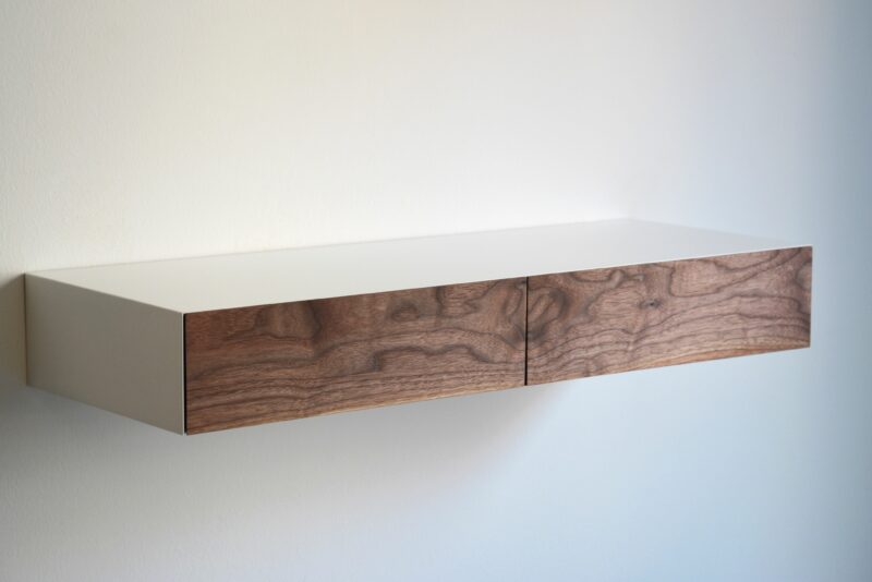 Schmale Schubladen weißer Schminkkommode aus Holz an der Wand